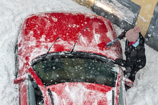 吹雪の大雪の後に運転するために雪に覆われた赤い車を掃除する女性の上面図