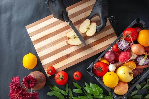 暗い表面でリンゴを切る上面図女性料理人