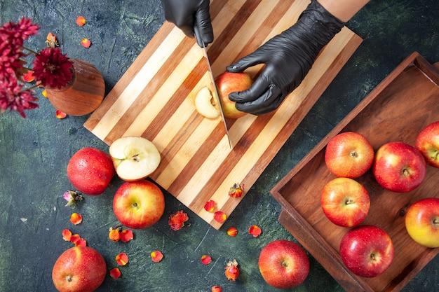 회색 표면에 사과를 자르는 상위 뷰 여성 요리사