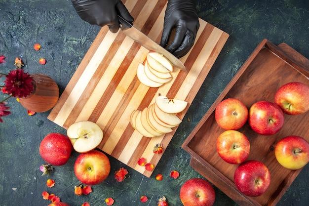暗い表面でリンゴを切る女性料理人の上面図