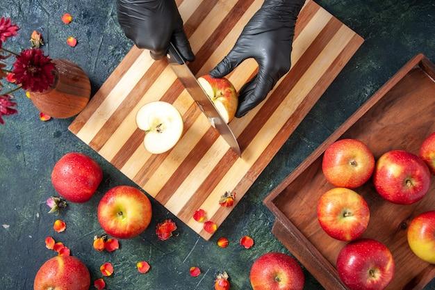 灰色の表面にリンゴを切る女性料理人の上面図