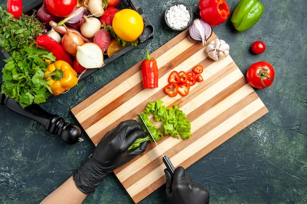 Cuoca vista dall'alto che taglia insalata verde fresca sulla superficie grigia