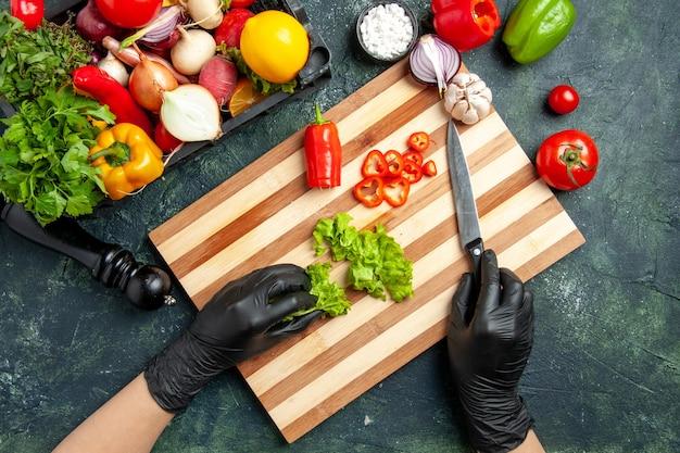 회색 표면에 신선한 녹색 샐러드를 자르는 상위 뷰 여성 요리사