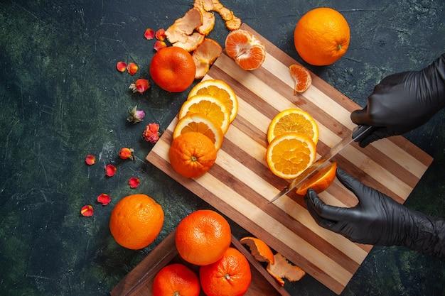 Top view female cook cutting orange on dark surface