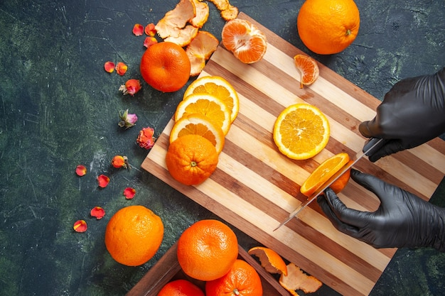 Top view female cook cutting orange on gray surface