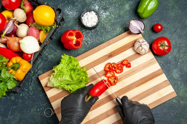 Top view female cook cutting red chilly pepper on gray surface