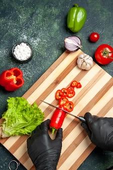 Cuoca vista dall'alto che taglia peperoncino rosso sulla superficie grigia