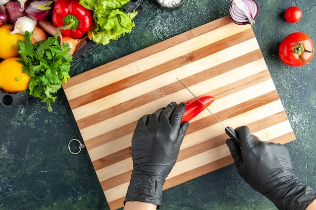 Top view female cook cutting red hot pepper on gray surface
