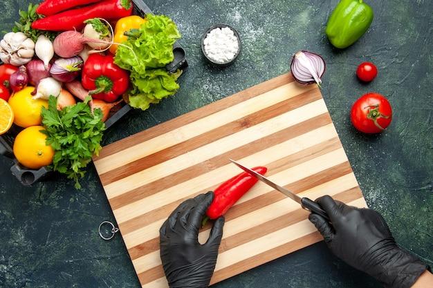 회색 표면에 붉은 고추를 자르는 상위 뷰 여성 요리사