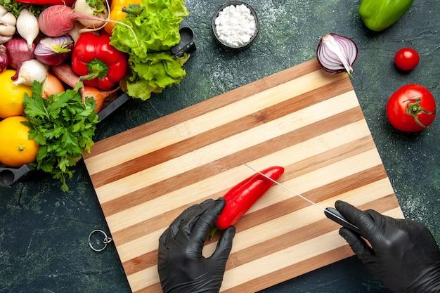 灰色の表面に赤唐辛子を切る上面図の女性料理人