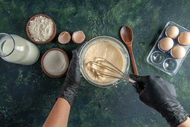 Top view female cook mixing up flour in plate with eggs on dark surface