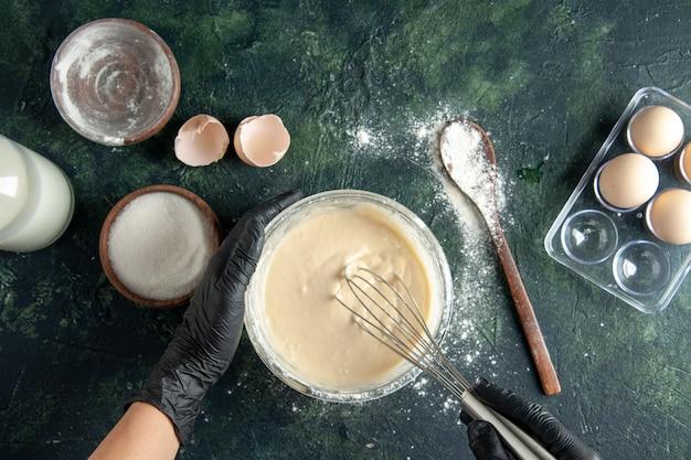 Женский повар, вид сверху, смешивает ингредиенты и делает тесто на темной поверхности Бесплатные Фотографии