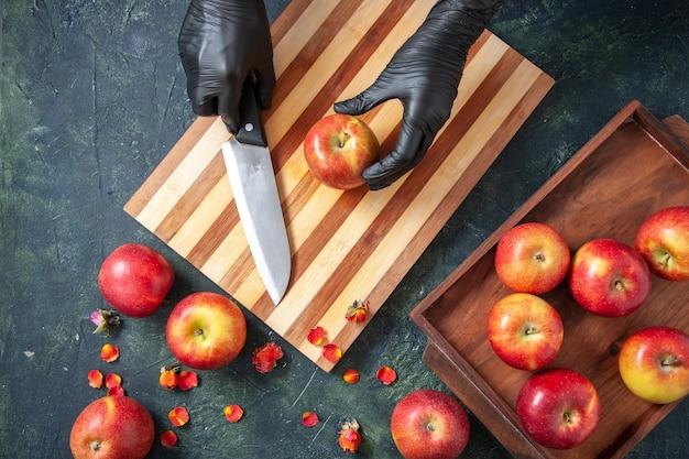 Cuoca vista dall'alto che si prepara a tagliare le mele su una superficie scura