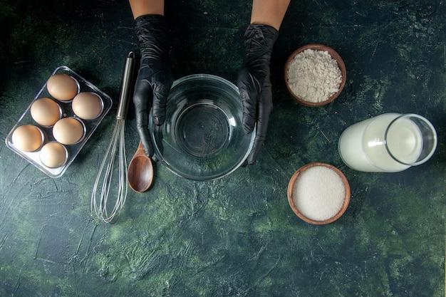 暗い表面でミルクの卵と小麦粉で何かを調理する準備をしている上面図の女性料理人