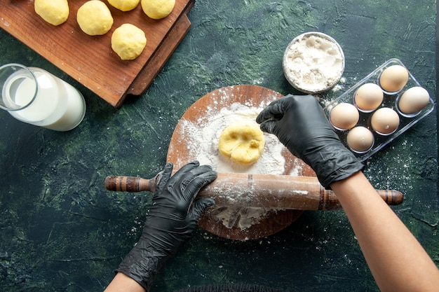 暗い表面に小麦粉で生地を展開する上面図女性料理人