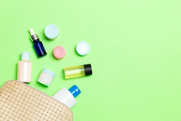 Top view of female cosmetics bag on green background