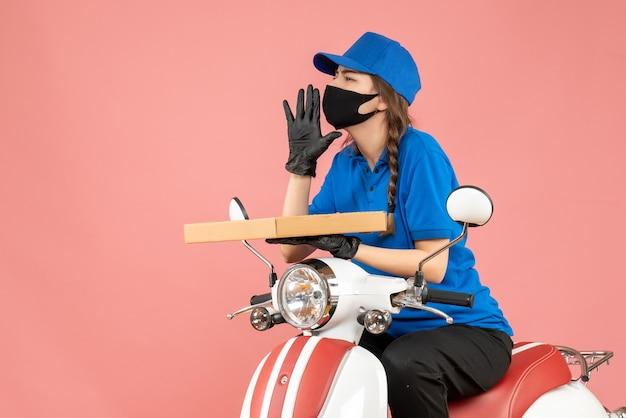 Vista dall'alto del corriere femminile che indossa maschera medica e guanti seduto su uno scooter che consegna ordini chiamando altri su sfondo color pesca pastello