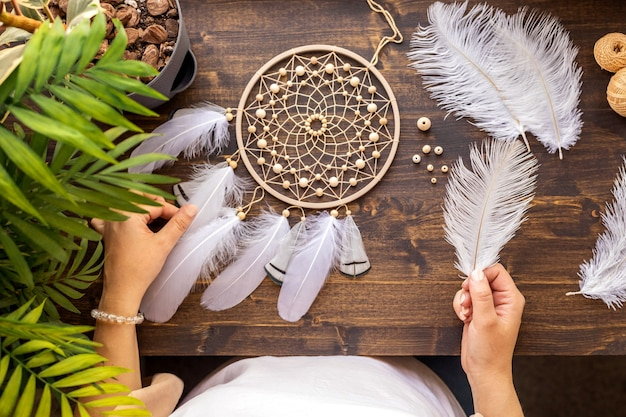 Top view female craftsman hands creating traditional dreamcatcher choosing material at workshop