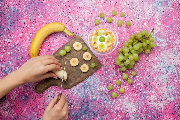 Вид сверху женщина нарезает бананы вместе с виноградом и пирогом на фиолетовой поверхности фруктовый сахар сладкий