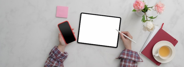 Top view of female freelancer working on blank screen tablet and smartphone on marble desk