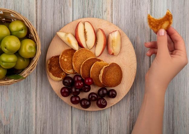 Vista superiore della mano femminile che tiene pancake morso e frittelle con ciliegie e pesche a fette sul tagliere con cesto di prugne su fondo di legno