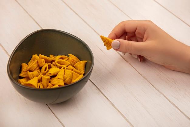 Vista superiore della mano femminile che tiene gli spuntini di mais a forma di cono con una ciotola di patatine su un tavolo in legno beige