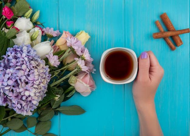 Vista superiore della mano femminile che tiene una tazza di tè con fiori freschi di stecca di cannella isolati su un fondo di legno blu