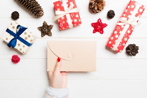 Top view of female hand holding an envelope new year decations. christmas time concept