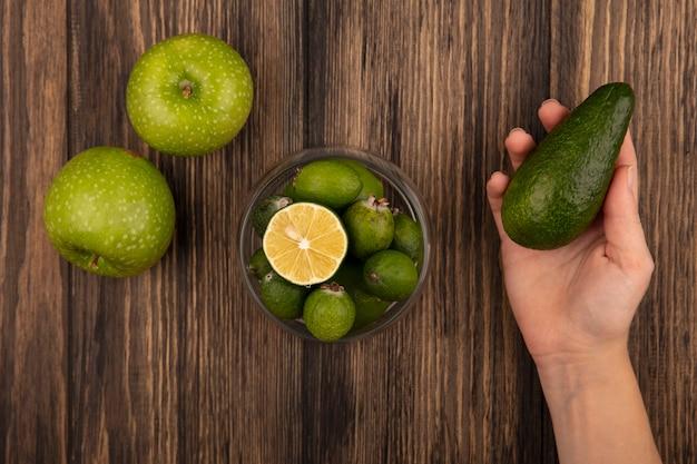 Vista dall'alto della mano femminile che tiene un avocado fresco con feijoas su una ciotola di vetro con mele verdi isolato su una parete in legno