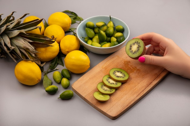 Top view of female hand holding fresh kiwi on a wooden kitchen board with kinkans on a bowl with lemons isolated on a white background