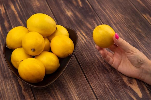Vista dall'alto della mano femminile che tiene un limone fresco con una ciotola di limoni su una parete di legno