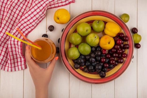 Vista superiore della mano femminile che tiene il succo di pesca fresco con una ciotola con frutta fresca come prugne di ciliegia verde, ciliegie rosse, pesche dolci su un fondo di legno bianco