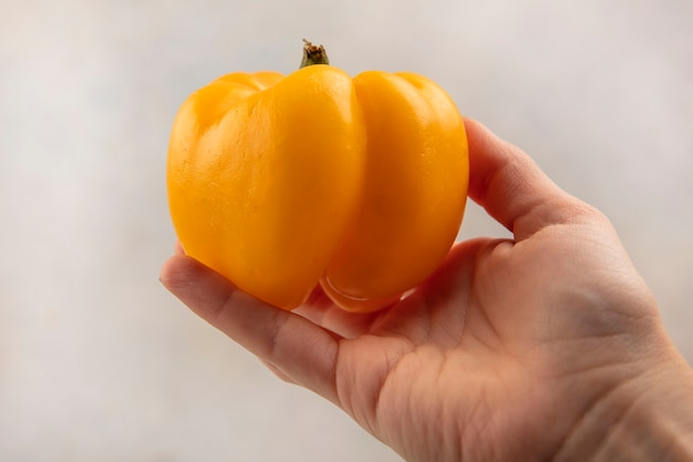 Top view of female hand holding a fresh yellow bell pepper on a white surface