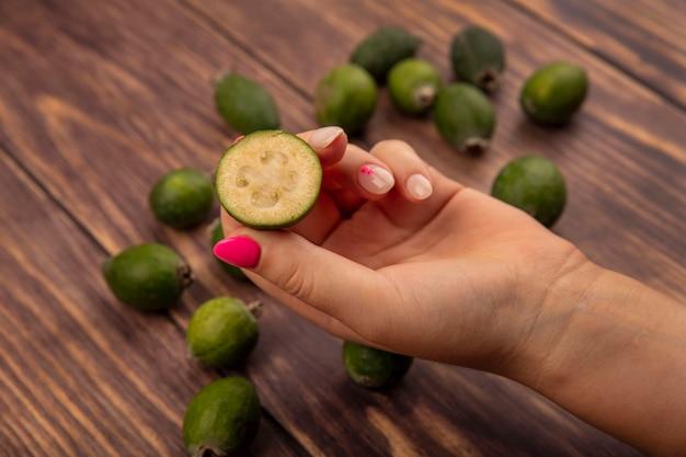Vista superiore della mano femminile che tiene un feijoa mezzo fresco con feijoas isolato su una superficie di legno