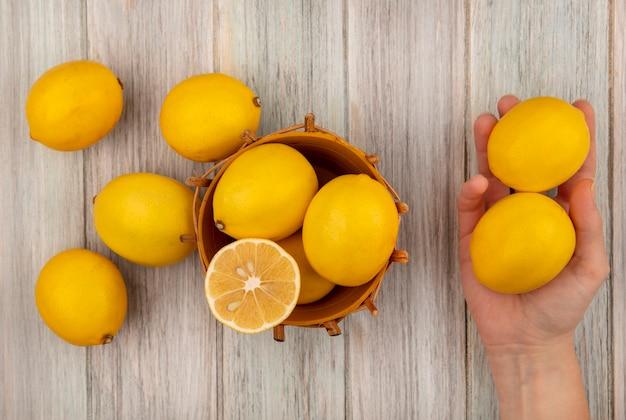 Vista superiore della mano femminile che tiene i limoni con i limoni su un secchio su una superficie di legno grigia