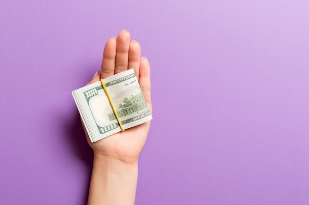 Top view of female hand holding a lot of rolled up dollar banknotes on colorful background. poverty concept. credit concept with copy space