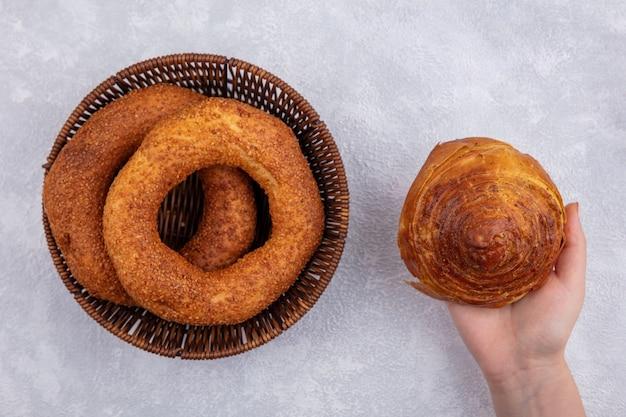 Vista superiore della mano femminile che tiene la pasticceria nazionale azera gogal con un secchio di bagel turchi su sfondo bianco