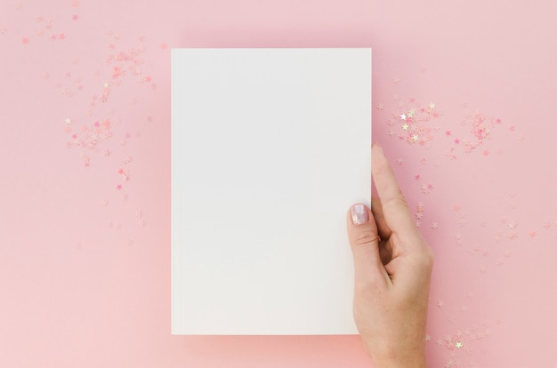 Top view of female hand holding notebook