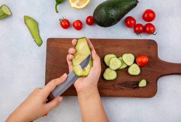Vista dall'alto della mano femminile che tiene in una mano avocado e nell'altro coltello a mano sulla tavola di cucina in legno con fette di cetriolo pomodorini limone isolato su bianco