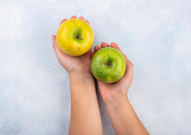 Vista dall'alto della mano femminile che tiene in una mano mela verde e nell'altra mela gialla su bianco