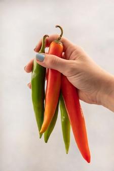 Vista superiore della mano femminile che tiene i peperoni lunghi arancioni e verdi su una superficie bianca