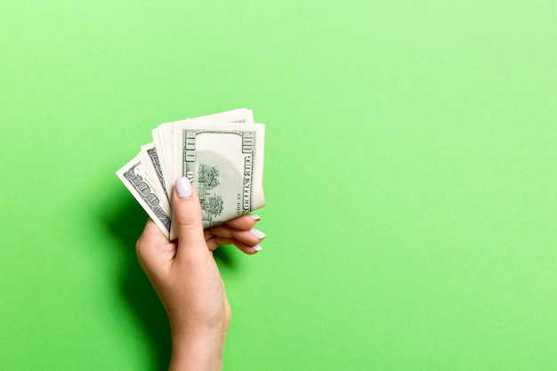 Top view of female hand holding a pack of money on colorful background. one hundred dollars. business concept with empty space for your design. charity and tips concept