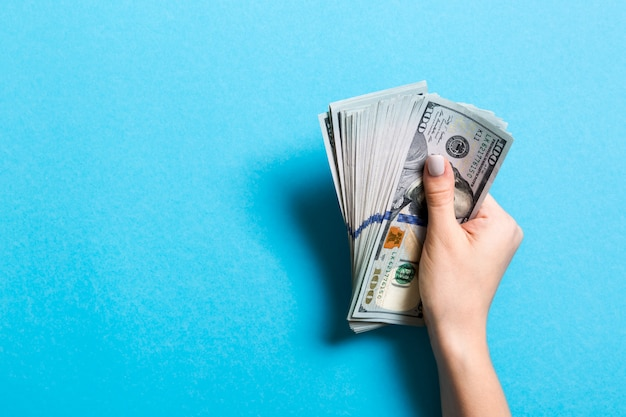 Top view of female hand holding a pack of one hundred dollar bills on colorful background