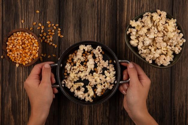 Vista dall'alto della mano femminile che tiene una padella con popcorn con chicchi di mais su una ciotola di legno su un tavolo di legno