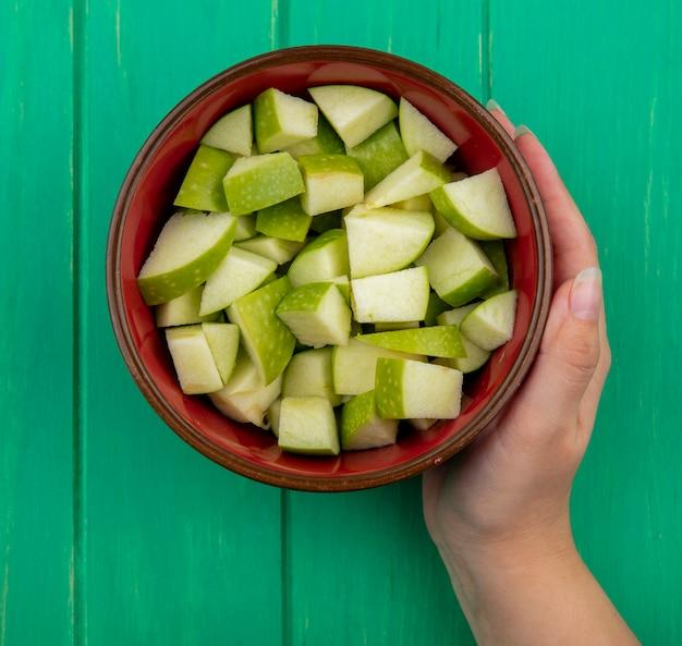 Vista dall'alto della mano femminile che tiene una ciotola rossa di mele tritate sul verde