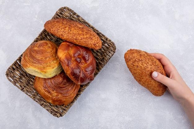 Vista dall'alto della mano femminile che tiene tortino di sesamo con un secchio di panini diversi su uno sfondo bianco