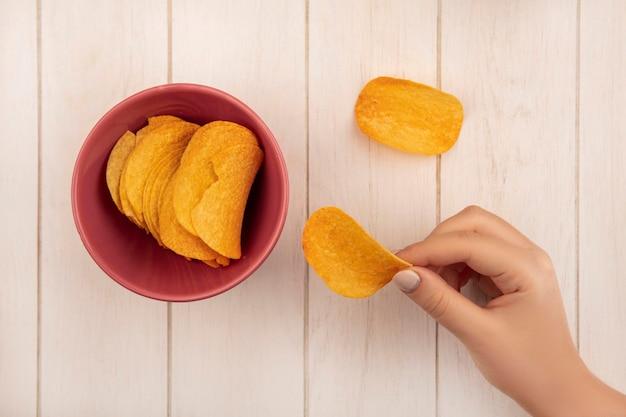 Vista dall'alto della mano femminile che tiene gustose patatine croccanti su un tavolo di legno beige
