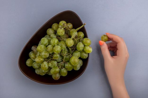 Vista dall'alto della mano femminile che tiene l'uva bianca berrie con ciotola di uva bianca su sfondo grigio