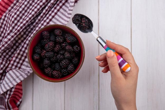 La vista superiore della mano femminile tiene il cucchiaino da tè con una mora con un tovagliolo a quadretti rosso su una superficie bianca
