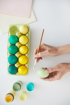 Top view of female hand painting easter eggs in pastel green and yellow colors over white background, copy space
